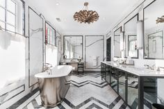 Black and white marble bathroom | Master bathroom boasts a black mirrored makeup vanity paired with a stool placed under a black framed mirror | #bathroomideas #bathroomdecor #bathroomdesign