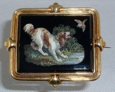 "Micromosaic of a spaniel and duck C. 1820-1830s A superb micromosaic of a spaniel flushing a duck from the reeds. Set in a 18K gold frame, the pin is 2 1/2"" by 2"" (the black glass and mosaic section is 2"" x 1 3/4"". The tiles are curved in order to create the fluid lines in the dog's fur and the reeds."