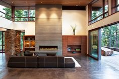 Living Room - Contemporary modern open concept recognizing the importance of shape, form and function.  Stone fireplace with wrap around natural wood cabinetry and an awesome view.  Gorgeous and cleverly conceived.   (re-pinned photo only from Martis Camp House by Concreteworks)
