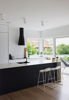 Simpel kitchen with white Corian-countertops and wide windows to the garden. The windows let the natural light shine in.