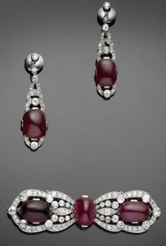 An art deco ruby, tourmaline and diamond brooch and earring suite, by Van Cleef & Arpels, circa 1930.  The brooch set to the centre with a sugarloaf ruby, between elongated scalloped terminals, set with a large cabochon ruby, a large oval cabochon tourmaline and old brilliant and single-cut diamonds in millegrain and collet settings, the pendent earrings of similar design, mounted in platinum, brooch signed Van Cleef & Arpels Paris, French assay mark