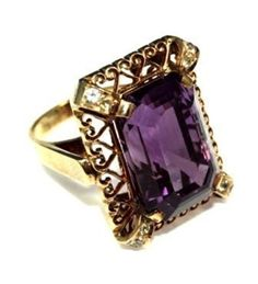 """RING,  an amethyst dress ring having a rectangular trap cut amethyst in a claw setting and surrounded with a """"pierced-work"""" setting and back rail.  Two colourless topazes are set in each claw.    The amethyst is approximately ca 26.99ct. The ring is in an unhallmarked yellow metal tested and valued as if 18ct gold. Gross weight 17.51 grams."""