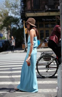 Sky blue maxi dress, brown sunhat, and chunky gold watch.
