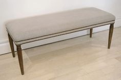 Upholstered bench with circular tapered turned legs. The seat upholstered with Belgian linen and nail head trim. Belgium, circa 1950.