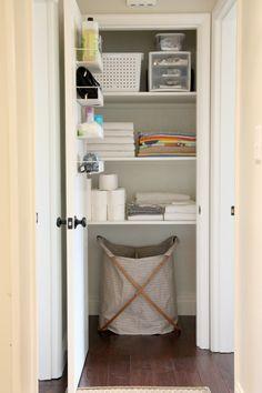 organizing linen closet: hamper, drawers, totes, hanging rack