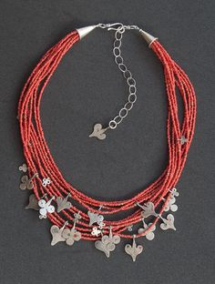 Angela Lovett Designs   Antique silver Sahrawi amulet charms adorn 11 strands of antique red white-heart beads. http://www.angelalovett.com