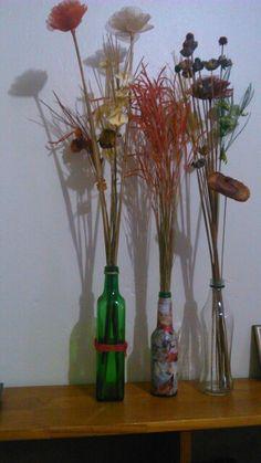 Flores artesanais do cerrado decorando uma simples garrafa de azeite e cerveja.