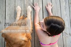 A young girl and a golden retriever dog side by side on a jetty.  – Image © Masterfile.com: Creative Stock Photos, Vectors and Illustrations for Web, Mobile and Print