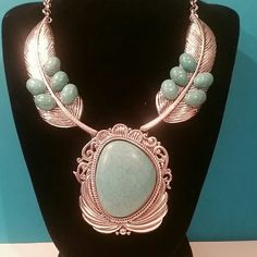 Turquoise & Feather Southwest BoHo Necklace Set Beautiful Metal Silvertone Feather Necklace with Simulated Turquoise Accent Stones. While this is NOT the high priced Necklaces you see that are made by the Native Americans, it is certainly not a piece to be overlooked. Yes, this is HIGHER end Boutique Costume Jewelry and you won't be disappointed! You can own this gorgeous Necklace without paying the hundreds of dollars to get it.  **Matching Earrings INCLUDED.*** Jewelry Necklaces