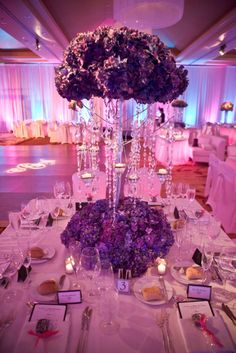 This spring time wedding at The Ritz-Carlton, Denver included various shades of purple - from linens and lighting effects  to stunning flower arrangements -  all creating a warm glow in the ballroom.