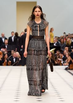 Black long dress with capelet shoulders worn with black chain detail strap sandals. Discover the collection at Burberry.com