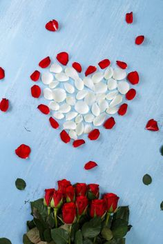heart of red rose petals on blue wooden board