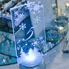 Heinrich and Casey�s whole day had a distinctive winter wonderland theme to it, from white rose petals scattered around to fake snow on the reception tables. Sparkling crystals gave an icy effect, and white branches and silvery snowflakes added to the vibe.The couple also had a dry ice machine and sparklers to add to the wintery style of the day, and blue lights were used to emphasise the colour scheme. Each guest received a glass engraved with snowflakes and the couple�s names and wedding…