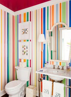 The powder room on the main floor is used by guests as well as the kids, who often use it to brush their teeth in the morning. With a deep fuchsia lacquer on the ceiling and candy colored stripes on the walls, the space brings in every color found in the house and does not take itself too seriously.