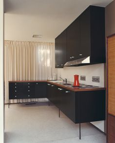 Unsightly service elements of the kitchen are tucked into the central core of the home, while a furniture-like L is situated in the rear corner and visible from the living area. Stevens had the 42 George Nelson cabinet pulls made with a CNC-router system