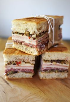 Muffaletta sandwiches cut into rectangles, perfect for a picnic! Muffaletta Sandwich - All the nutrition you need and then some. Bring a bit of the Mediterranean to your office lunch with this tasty Muffaletta recipe. Sandwich Bar, Soup And Sandwich, Salami Sandwich, Muffuletta Sandwich, Chicken Sandwich, Central Grocery Muffaletta Recipe, Focaccia Sandwich Recipe, Hamburgers, Finger Food