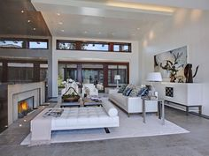A concrete hearth branches out into a gray tile floor. White chairs, sofa and chaise lounge provide ample seating.