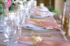 The bride's background in interior design aided in the construction of the linens, from Wildflower Linen, to create the delicate lace overlay onto a romantic blush chiffon fabric. Accents of gold tipped the china, chargers, stemware, flatware, and decorated the napkin holders adding a golden-hue to the refined and precisely perfect tablescape that carried into the design of the Persian Sofreh. Photos: Braja Mandala. Coordinator: Wedding Elegance by Nahid. Florals: Adorations Botanical…