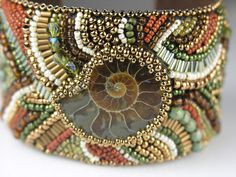 The focus of this wide cuff is a beautifully preserved Ammonite Fossil. The warm colors in the Ammonite are repeated with embroidered crystals, Bead Embroidered Bracelet, Embroidery Bracelets, Beaded Cuff Bracelet, Bead Embroidery Jewelry, Beaded Embroidery, Cuff Bracelets, Seed Bead Jewelry, Beaded Jewelry, Handmade Jewelry