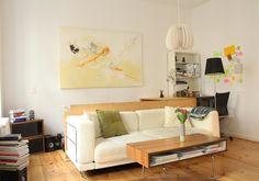 Einrichtungsidee für ein helles Wohnzimmer: cremefarbene Couch, Couchtisch, Bücherstapel sowie großer Kunstdruck.  2-Zimmerwohnung in Berlin.  #Berlin #Kreuzberg