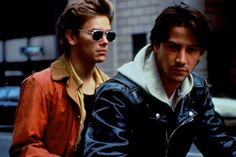 Scott Favor (Keanu Reeves) in his signature orange jacket and Mike Waters (River Phoenix) in a leather jacket with hooded sweatshirt in My Own Private Idaho.