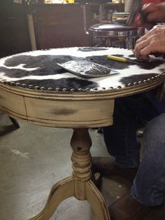 Our most recent work in progress. Refinished side table with a cowhide top.