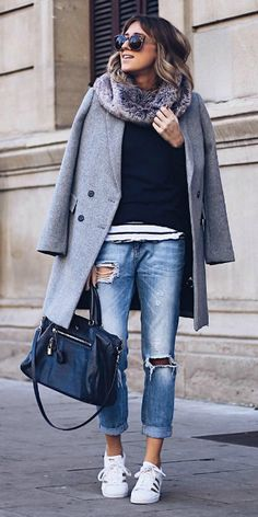 Ane Hernando + pair of faded denim jeans + rip detailing + rolled at the ankle + gleaming Adidas sneakers + navy blue top + oversized boyish grey coat   Shoes: Adidas.