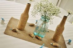 Brittany:Great simple table decor, clear mason jar, burlap band with deep purple ribbon, babys breath, sage and single orchid