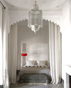 In a guest room, the lamp is from the 1950s, the lantern is Moroccan, and the throw was found in a local shop; the molding is original to the house.