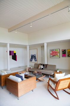 Although this room is simple it also has so much to look at, with modern art on the walls and funky wooden living room furniture. We love it.