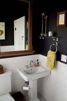 bathroom.  black walls with white subway tile dado.