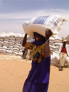 woman carries sack of food aid from the European Union ~ Ouaddaï, Chad. March 2009