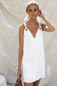 The perfect cute and comfy go-to outfit! The Barca Dress is made from a lightweight linen blend fabric in an off white hue. It is a shift style and features a V neckline, gold eyelet strap holes with adjustable straps and buttons at centre front. Complete the look with tan boots and a a hat! By Sabo Skirt.