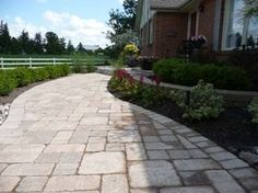 A formal brick walkway leads to the front of this house. It has nice subtle curves to border the beds on each side of it. Notice the repetition