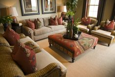 Plush living room in brown and red design.  There is one brown sofa and four armchairs all surrounding a patterned ottoman serving as a large coffee table.  Brown and red patterned pillows throughout.