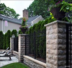 Retaining walls can also be privacy fences. These wall units are integrated with slat fence and tall evergreens to provide security and privacy.