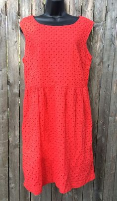 "Red sleeveless dress from George, size 12. This dress is ""Rock N Red"" and has an eyelet and embroidered circle design. The outer is 100% cotton, and the lining is 100% polyester. There is a zipper and clasp closure on the back (about 18"" zipper with hook and loop clasp at the top, all hidden in the back seam). 