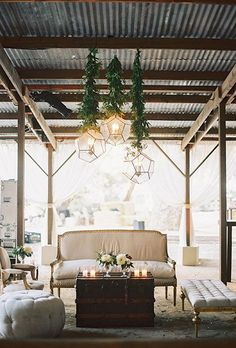 A rustic-chic lounge area with couches, benches, and geometric chandeliers | Brides.com