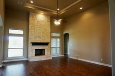 Large living room, hardwood floors, pop-up in ceiling with crown moulding, floor to ceiling stone fireplace, stained mantle, stone hearth, open concept floorplan #mcbeehomes