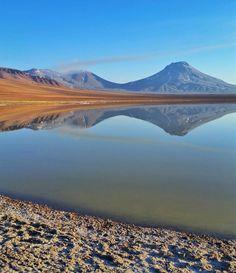 Hoje o nosso dia no Atacama começou com um café da manhã na Laguna Lejia antes de subir o Vulcão Lascar com a equipe da @aylluatacama. O Vulcão Lascar é esse da esquerda que está saindo uma fumaça. É um vulcão ativo e a subida até sua cratera é bem difícil pois a cratera está a quase 5500 metros de altitude. Você acha que a gente conseguiu subir o vulcão e chegar até a cratera? Dê seu palpite!  Quem quiser antecipar a resposta assista o Snapchat nerdsviajantes ou Instagram Stories…