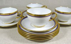 Limoges porcelain dessert service includes four dessert plates and three teacups w/saucers, in the Seville pattern, featuring gilded laurel trim and cobalt blue banding. One cup and saucer, in the Nantes pattern, has gold banding only. All twelve pieces are unused and in pristine condition, they're individually back stamped Vignaud Limoges France.  SIZE: Desert plates - 6.25in diameter x .75in, Teacups - 3.5in diameter + handle x 2.25in, Saucers - 5.75in diameter x .75in,  SOLD