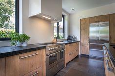 Houten keuken met zwart natuursteen blad en moderne apparatuur. #hout #maatwerk #wood #kitchen