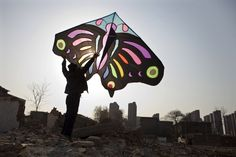 March 24, 2012. A man holds up a kite at a demolition site near residential areas in Shijiazhuang, Hebei province, China.