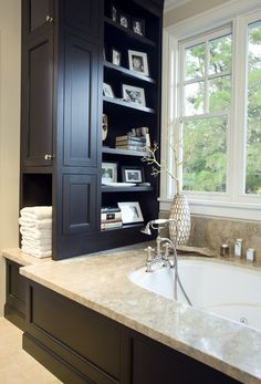 This slim structure packs in a lot of function, from the cabinet and towel cubby on one side to the open shelving on the other. Small slices of space like this, often lurking next to a sink, tub or mirror, cry out to be put to use. I'm going to do something similar next to my bathroom sink, with a closed door similar to a medicine cabinet with deep shelves and electrical outlets for all of my hair appliances and make-up.