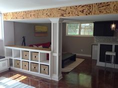 half-wall with wood beam and built-in shelving