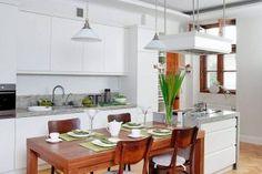 Meble kuchenne. Efektownym kontrastem dla bieli szafek sięgających aż do sufitu jest stół z drewna orzechowego i dębowy parkiet. - zdjęcie