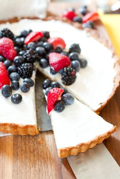 The BEST healthy summertime dessert! This tart is grain-free, filled with creamy Greek yogurt and piled high with loads of fresh berries!