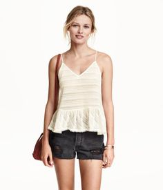 Camisole top in a loose pattern knit. Short, A-line style with narrow shoulder straps, V-neck, and ruffle at hem.