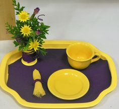 """Good Morning, Sunshine,"" tray that fits within 8"" square, by Jan Krass.  Purple knit tray liner, yellow linen napkin, melampodium and dianthus ""Siberian Blues.""  Foliage from Mexican heather.  Embroidery floss wrapped around container and napkin ring. Purple wire spirals.  Blue ribbon at FGCI State Show, June, 2016, Fort Dodge, IA."