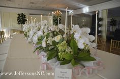 Elegant White Orchids with tall taper candles truly made this wedding a sight!